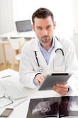 Portrait of a young doctor using tablet at work — Stock Photo