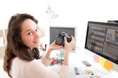 Young woman photographer watching pictures on camera  — Stock Photo