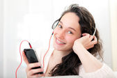 Portrait of a young attractive woman listenning music — Stock Photo