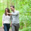 Young couple having a walk in a forest — Stock Photo #45908915
