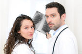 Young doctor and nurse analysing radiography — Stock Photo