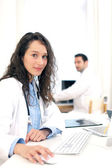 Doctor working at the office assisted with assistant — Stock Photo
