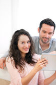 Happy young couple surfing on a tablet — Stock Photo