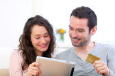 Young happy couple shopping on a tablet — Stock Photo