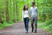 Young couple having a walk in a forest — Stock Photo