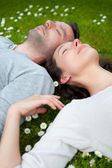 Attractive couple lying in grass at the park — Stock Photo