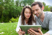Young beautiful couple using tablet at the park — Stock Photo