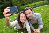 Young couple taking selfie picture at the park — Stock Photo