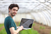 Young business farmer working on his laptop — Stock Photo