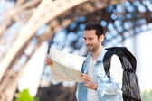 Young attractive tourist reading map in Paris — Stock Photo