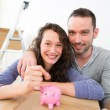 Young couple saving money in a piggy bank — Stock Photo #48845833