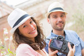 Young couple of tourist watching photographs — Stock Photo