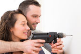 Attractive Man assisting his girlfriend using a drill — Stock Photo
