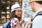 Young happy couple choosing postcards during holidays — Stock Photo