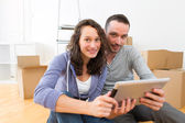 View of a Young couple using tablet while moving in new flat — Stock Photo