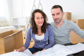 Young couple watching plans in their new flat — Stock Photo