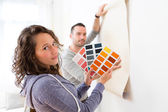 Young couple choosing colors of their wallpaper — Stock Photo