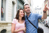 Young couple on holidays doing shopping — Stock Photo
