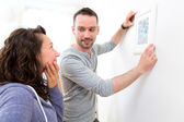 Couple hanging a painting in their new flat — Stock Photo