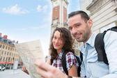 Couple of young attractive tourists watching map  — Stock Photo