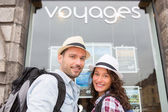 Young happy couple in front of travel agency — Stock Photo