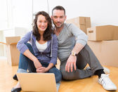 Young couple using laptop while moving in new flat — Stock Photo