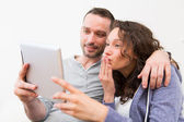 Young happy couple video calling on tablet — Stock Photo