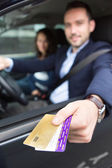 Couple in his car paying at a toll booth — Stockfoto