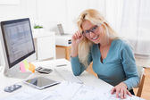 Blonde architect watching blueprint at the office — Stock Photo