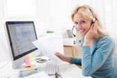 Young attractive blonde working in a call center — Stock Photo