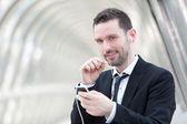 Portrait of an attractive businessman using handsfree set — Stock Photo