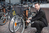 Businessman unlock his bike after a day of work — Foto Stock