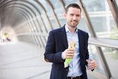 Young attractive man drinking coffee on his way — Stock Photo