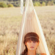 Woman in a field at sunset in the hammock — Stock Photo