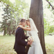 Bride and groom near the tree in the park — Stock Photo #40958619