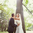 Bride and groom near the tree in the park — Stock Photo