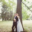 Bride and groom near the tree in the park — Stock Photo #40958643