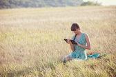 Mulher no campo com um laptop — Fotografia Stock