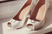 Wedding rings and bridal shoes — Stock Photo