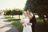 Bride and groom kissing in the park — Stockfoto
