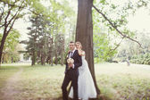 Bride and groom  near the tree in the park — 图库照片