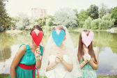 Bride and bridesmaids with colorful hearts — Stock Photo