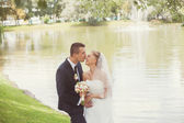 Bride and groom  in park near the lake — Stock Photo