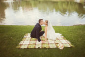 Bride and groom in  the park  near the lake — Stock Photo