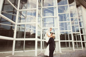Bride and groom posing near the glass building — Photo