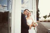 Bride and groom posing near the glass building — Foto de Stock