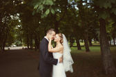 Bride and groom kissing in the park — ストック写真
