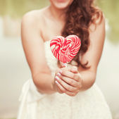 Bride  with candy in the form of heart — Photo