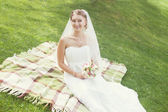 Bride  with  bouquet sitting  in the  park — Stock Photo