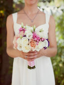 Bride in a white dress  with a bouquet — Stock Photo